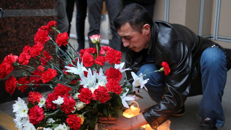A man leaves flowers during a memorial service for victims of a blast in St.Petersburg metro.