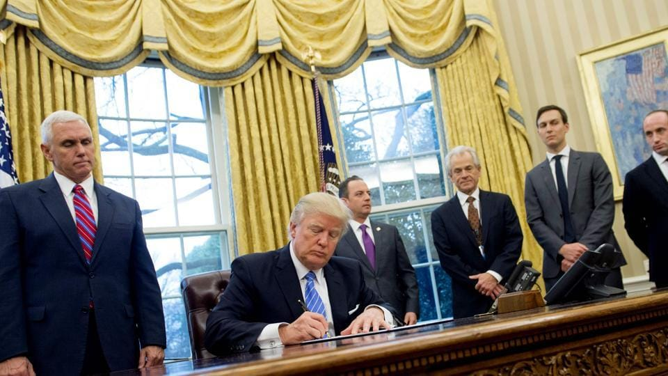 US President Donald Trump signs an executive order in the Oval Office of the White House in Washington, DC.