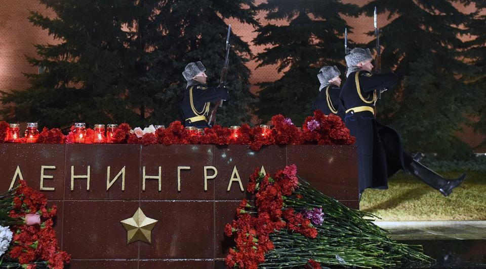 Flowers in memory of victims of the blast in the Saint Petersburg metro are seen at a memorial stone reading Leningrad by the Kremlin wall as honour guard soldiers march during the changing of the guards ceremony in central Moscow on April 3, 2017.