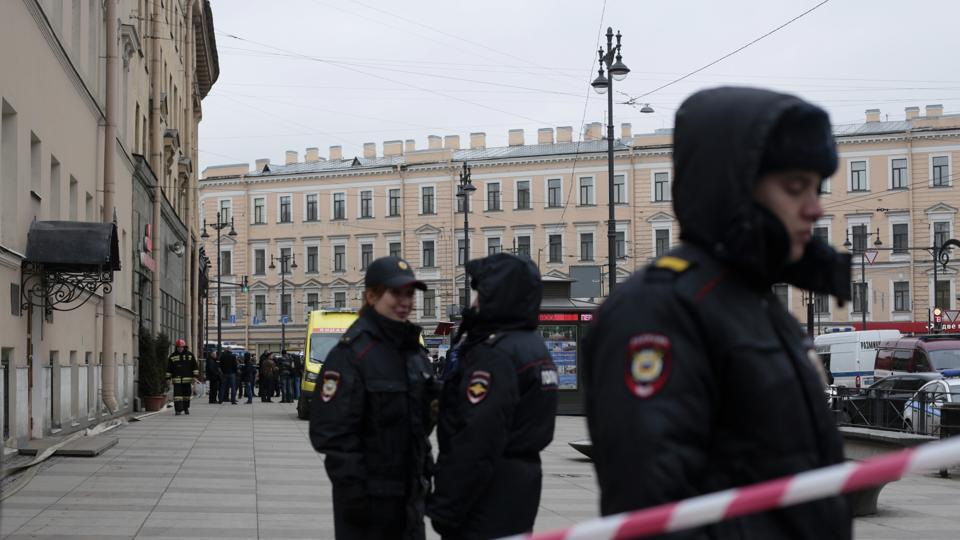 Russian police officers stand guard in a street after an explosion in St. Petersburg's subway.