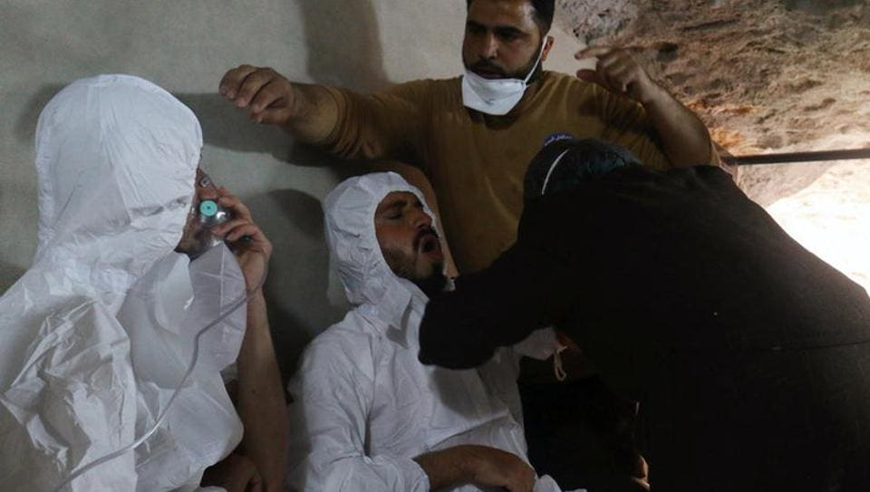 A man breathes through an oxygen mask as another one receives treatments, after what rescue workers described as a suspected gas attack in the town of Khan Sheikhoun in rebel-held Idlib, Syria April 4, 2017.