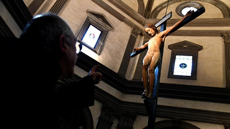 Father Giuseppe Pagano shows a wooden crucifix sculpted by Italian artist Michelangelo at the Santo Spirito basilica.