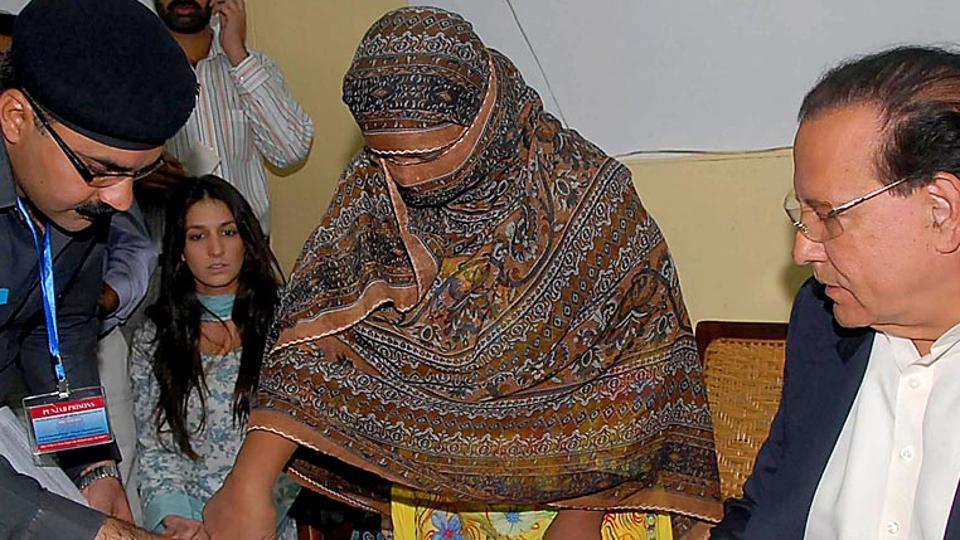 A file photograph shows Pakistani Christian mother Asia Bibi (C) places a thumb impression on her appeal papers against a death sentence, after she was sentenced to hang after being found guilty of insulting the Prophet Mohammed.