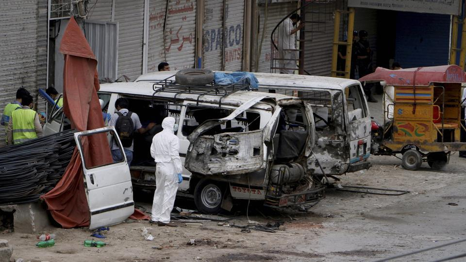 Pakistani investigators examine damage vehicles at the site of suicide bombing in Lahore, Pakistan, Wednesday, April 5, 2017.