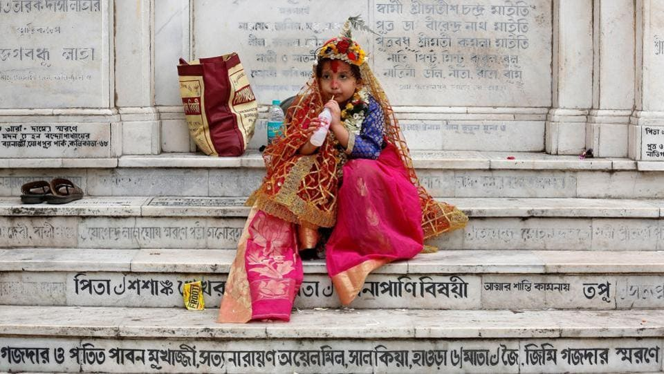 A girl dressed as Kumari, sipping a soft drink as she sits on stairs after attending rituals to celebrate the Navratri Festival inside the Adyapeath Temple, on the outskirts of Kolkata. (REUTERS)