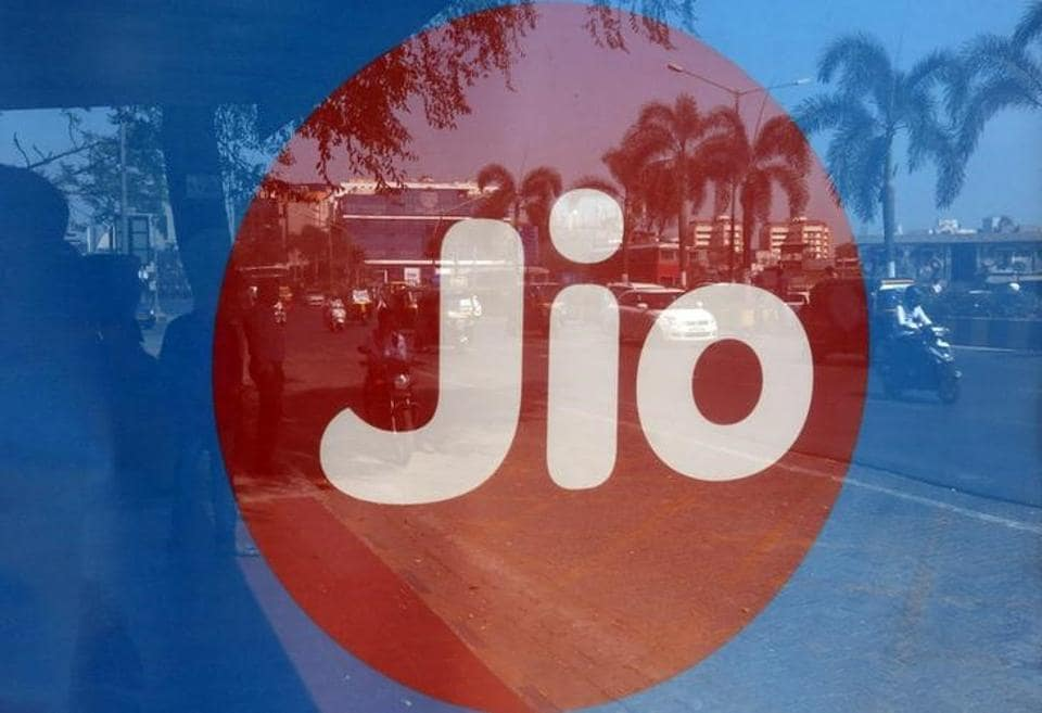 Commuters are reflected on an advertisement of Reliance Industries' Jio telecoms unit, at a bus stop in Mumbai, India, February 21, 2017.