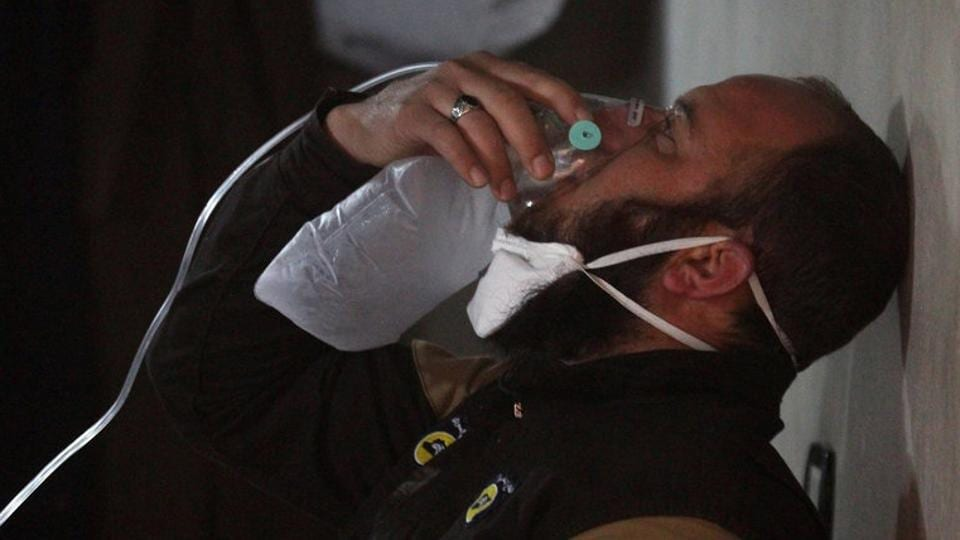 A civil defence member breathes through an oxygen mask, after what rescue workers described as a suspected gas attack in the town of Khan Sheikhoun in rebel-held Idlib.