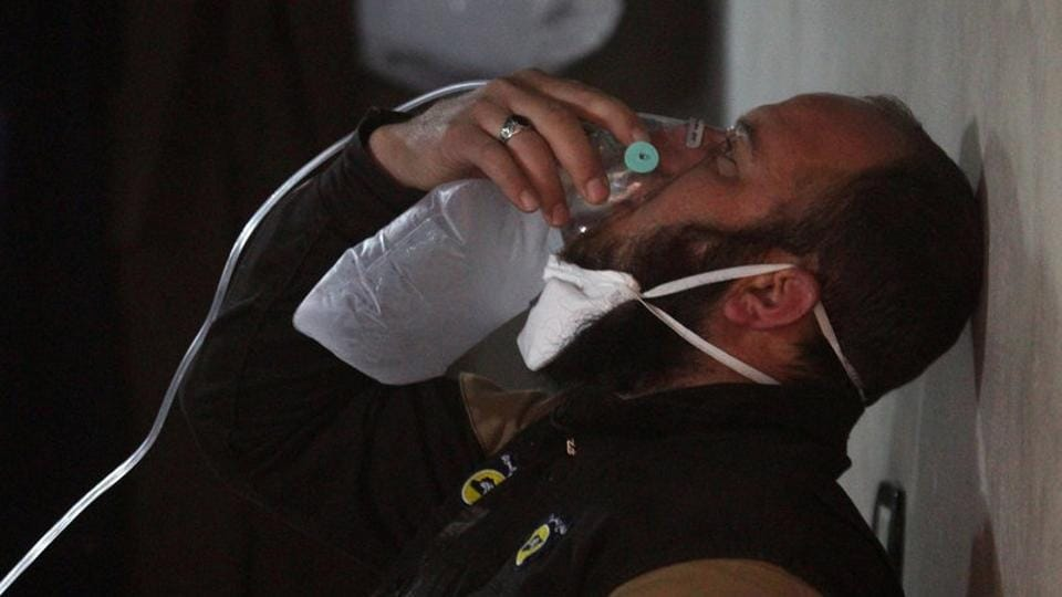 A civil defence member breathes through an oxygen mask, after what rescue workers described as a suspected gas attack . (Ammar Abdullah / REUTERS)