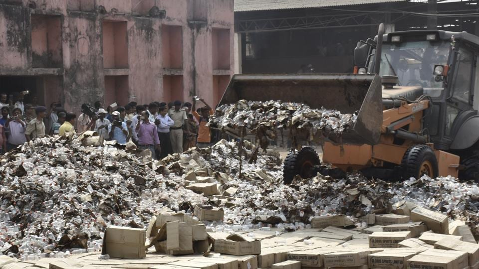 Bottles of country liquor being destroyed on the outskirts of Patna.