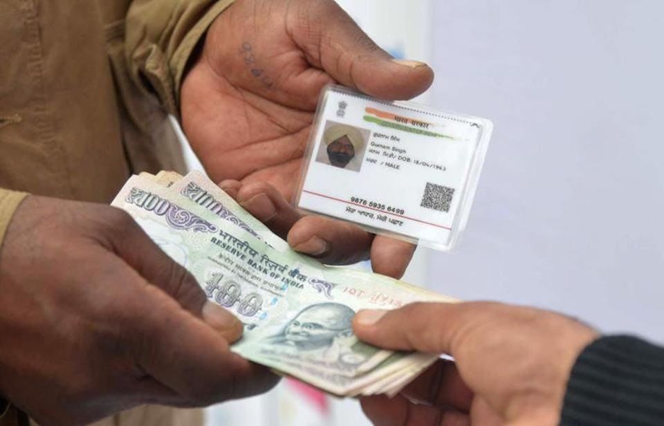An Indian visitor withdraws money from his bank account with an Aadhaar or Unique Identification (UID) card during a Digi Dhan Mela, held to promote digital payment, in Amritsar on January 6, 2017. / AFP PHOTO / NARINDER NANU