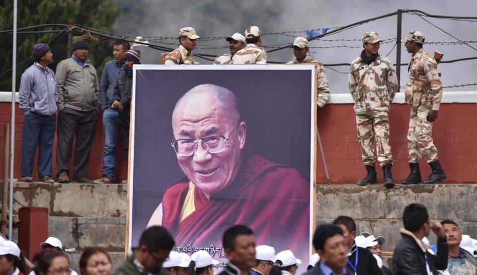 Security personnel stand beside a poster of Tibetan spiritual leader the Dalai Lama as he delivers religious teachings at the Buddha Stadium in Bomdila in Arunachal Pradesh on April 5.