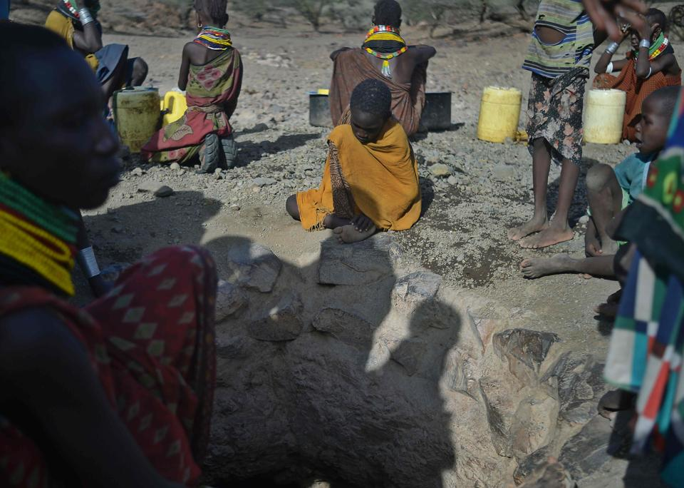 A young boy waits by the mouth of a rapidly drying waterhole near Lokitaung in northern Kenya's Turkana county where a biting drought has ravaged livestock population . (TONY KARUMBA / AFP)