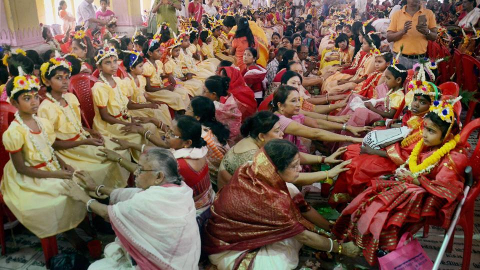 Devotees seeking blessings by touching feet of 'Kumari Kanya' (young girls) on the occasion of Ram Navami at Dakshineswar Ramkrishna Sangha Adyapeath, Dakshineswar, in Kolkata on Wednesday. More than 2000 girls participated in the Hindu festival that is observed after a nine days long fasting ritual. (PTI)