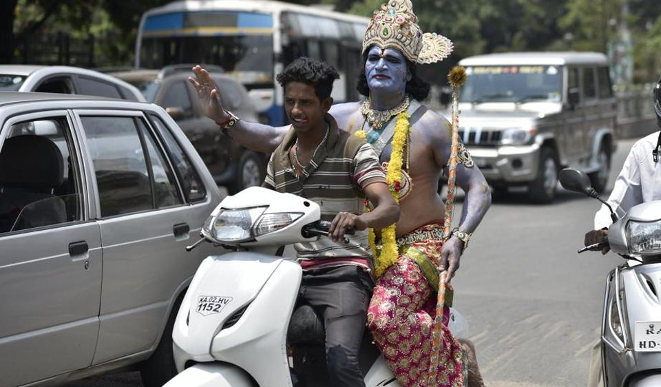 An artist dressed as Lord Ram rides pillion on a scooter before a road show on the occasion 9th day of Navratri at a Hanuman Temple near Kempegowda Railway Station in Bengaluru on Wednesday, April 5, 2017. (Arijit Sen/HT Photo)