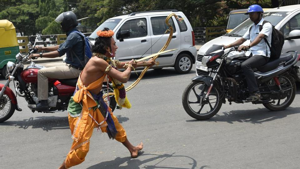 Artists dressed as characters of Ramayana performing amid traffic during a road show on the occasion 9th day of Navratri at a Hanuman Temple near Kempegowda Railway Station in Bengaluru. (Arijit Sen/HT Photo)