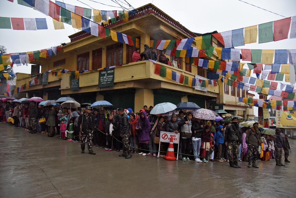 People stand in rain as they wait to welcome Tibetan spiritual leader Dalai Lama in Bomdila. (Anuwar Hazarika / REUTERS)