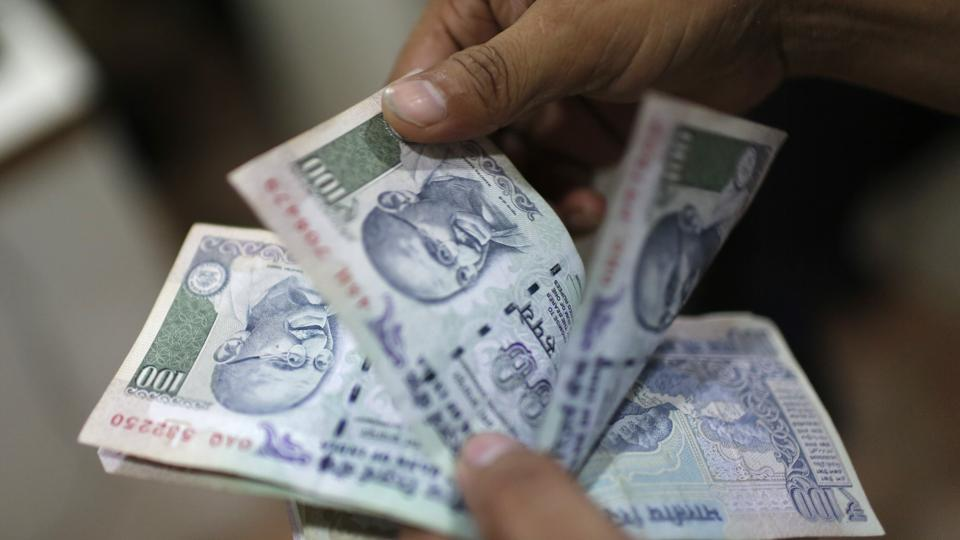 An employee counts Rs 100 notes inside a private money exchange office in New Delhi.