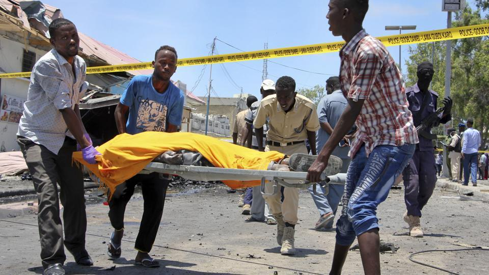 Somali men carry away the body of a civilian who was killed in a car bomb attack on a restaurant in Mogadishu, Somalia Wednesday, April 5, 2017.
