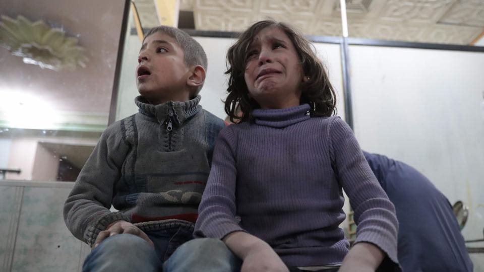 Syrian children wait to receive treatment at a makeshift clinic following reported air strikes by government forces in the rebel-held town of Douma.
