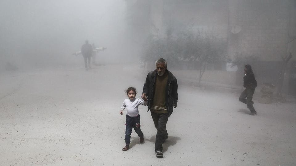 A Syrian man and girl flee following a reported government air strike on the rebel-controlled town of Hamouria, Syria.