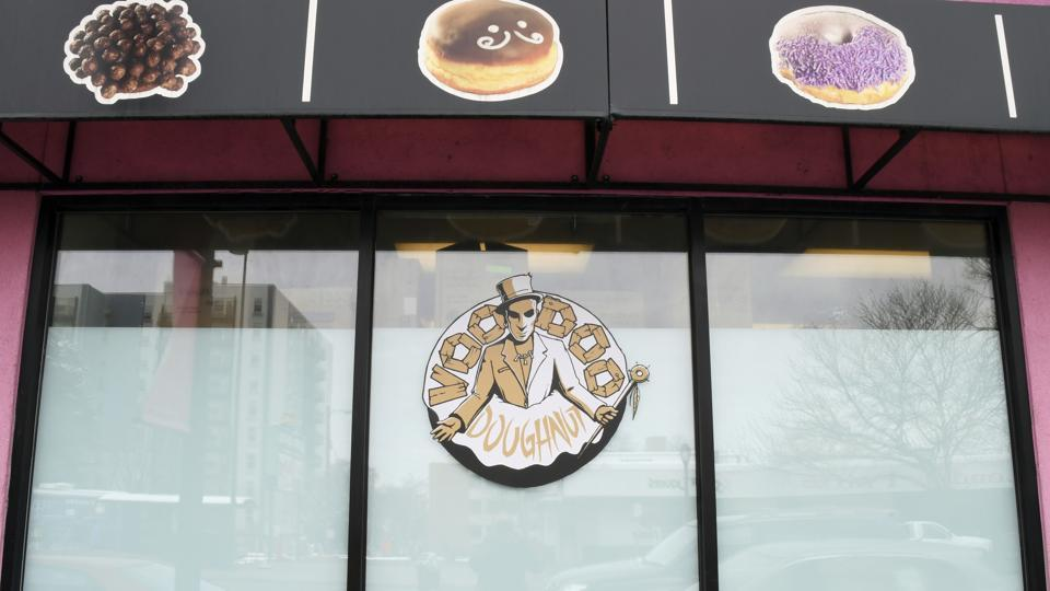 Images of the baked goods available adorn the windows of the storefront of Voodoo Doughnuts on East Colfax Avenue in Denver on Tuesday.