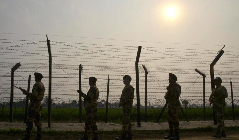 Indian Border Security Force (BSF) personnel patrolling along a fence at the India-Pakistan border.