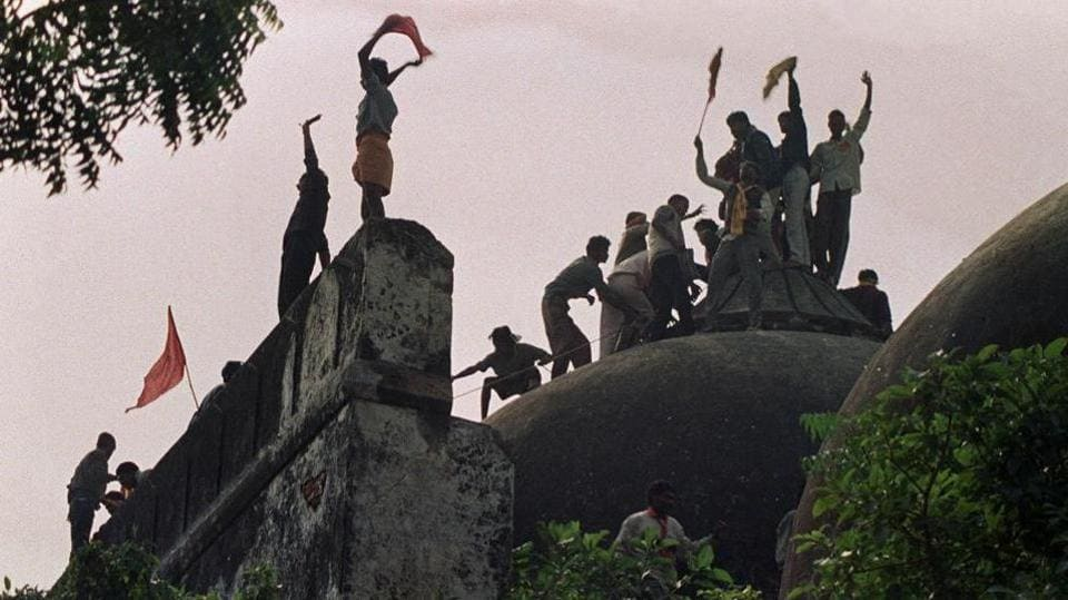 This file photo shows people shouting and waving banners as they stand on the top of a stone wall and celebrate the destruction of the 16th Century Babri Masjid in Ayodhya. (AFP File Photo)
