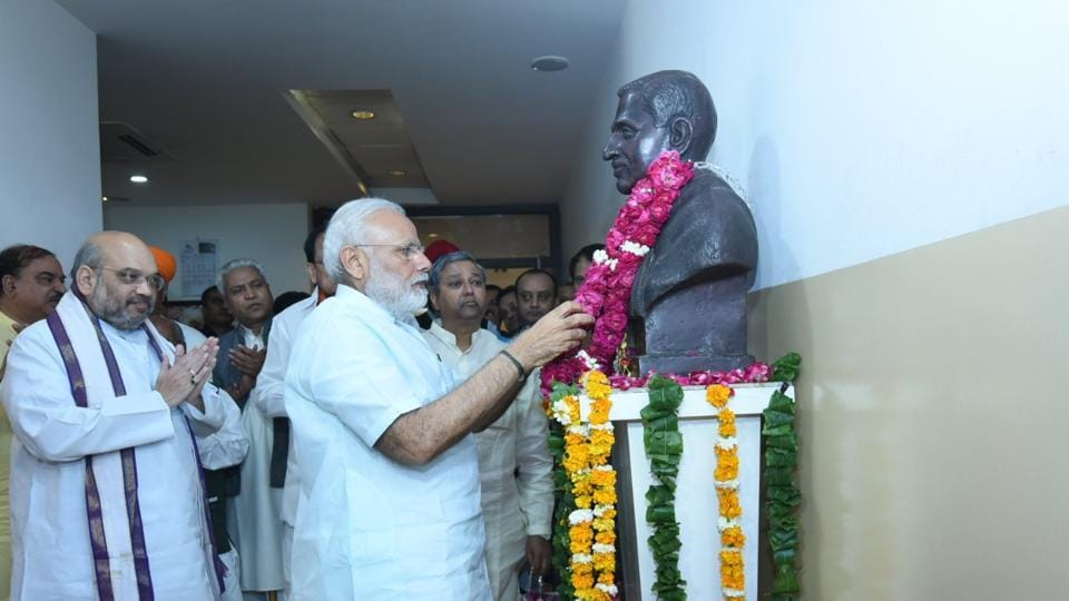 Prime Minister Narendra Modi pays tribute at Deen Dayal Upadhyay's statue at the party headquarters in New Delhi on Thursday.
