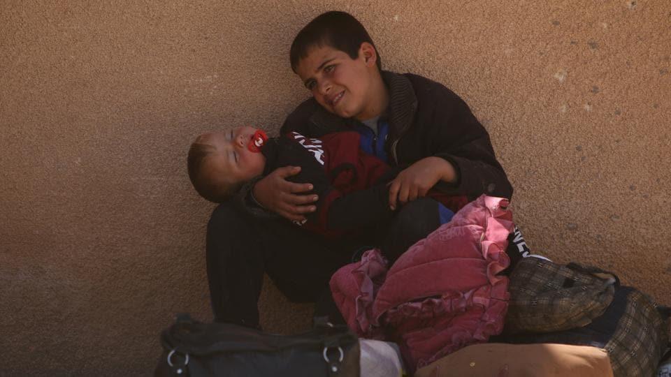 A boy, who fled from Raqqa city, carries a child near belongings in al-Mahmudli village, west of Raqqa, Syria.