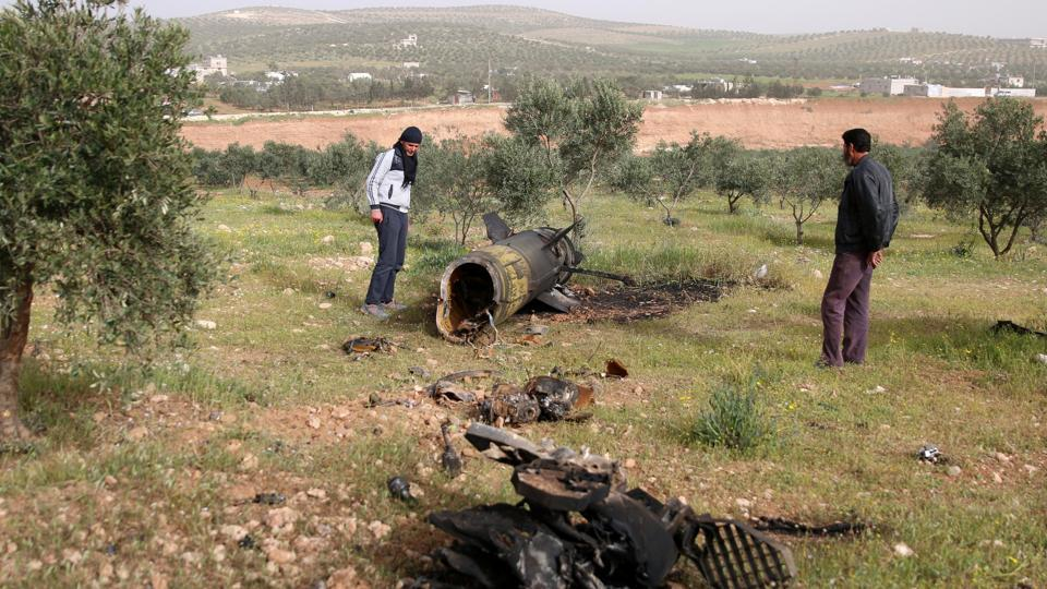 Men inspect a piece of a rocket that landed south of Daraa Al-Balad in Syria.