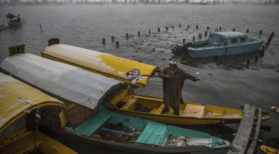 A Kashmiri boatman clears snow from shikara on the shores of the Dal Lake.The snowfall and rains over the past three days have forced the state government to close schools in the Valley till Sunday. (Dar Yasin / AP)