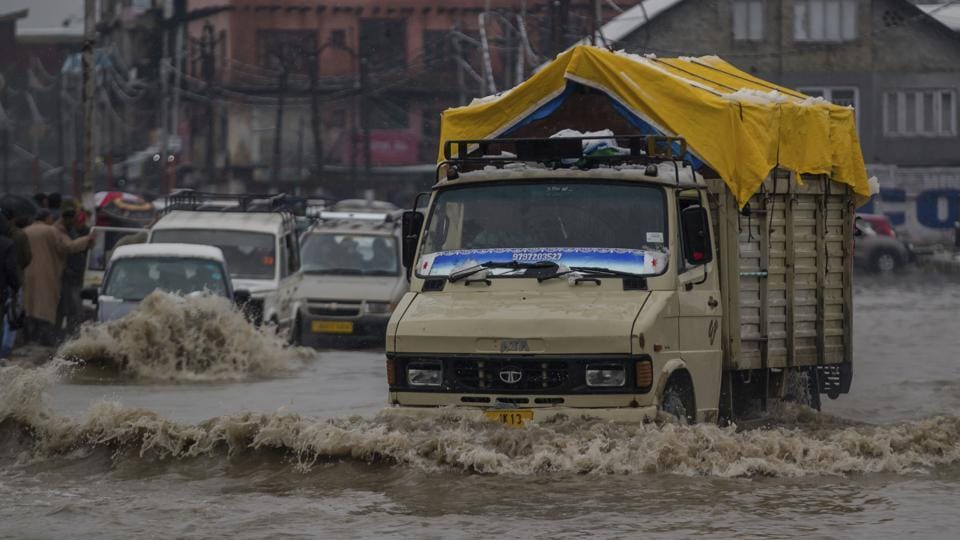 Vehicles navigate their way through a waterlogged street in Srinagar. Shooting stones and landslides at several places along the Jammu-Srinagar national highway has forced the closure of the road as well. (Dar Yasin / AP)