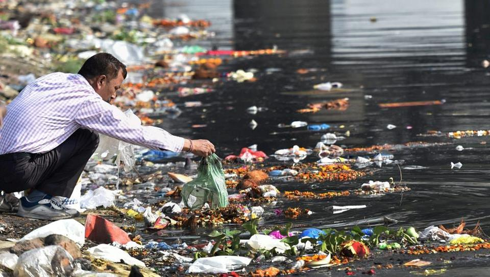 A man throws the puja offerings in Yamuna River at the end of Navratri festival in New Delhi. As the festival of Navratri ended,  the rivers  are once again in complete mess with several tonnes of flowers, polythene packets and other religious offerings floating on water. (Manvender Vashist  / PTI)