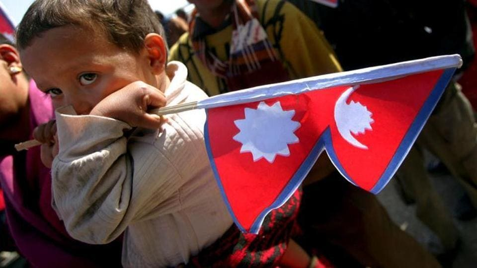 A file photo showing a Nepali child holds a flag during a rally in Kathmandu.