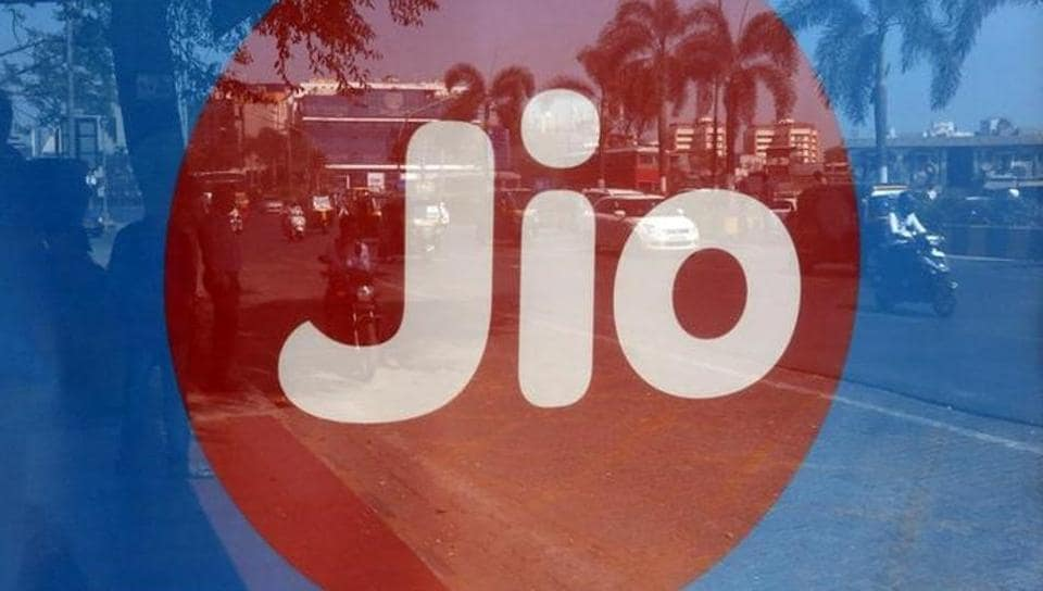 Commuters are reflected on an advertisement of Reliance Industries' Jio telecoms unit, at a bus stop in Mumbai.