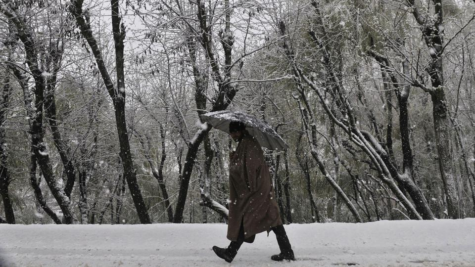 A man walks during snowfall on the outskirts of Srinagar.Kashmir Valley reeled under unprecedented rain and snow that swelled rivers and inundated vast areas.