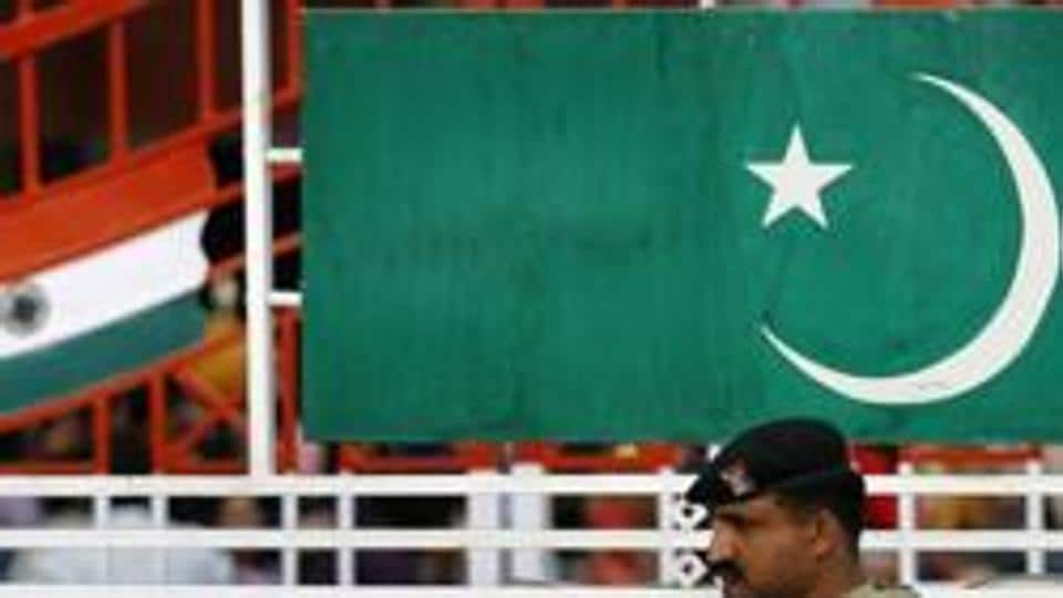 A file photo of Pakistani Ranger stands near the Pakistani flag and Indian flag.