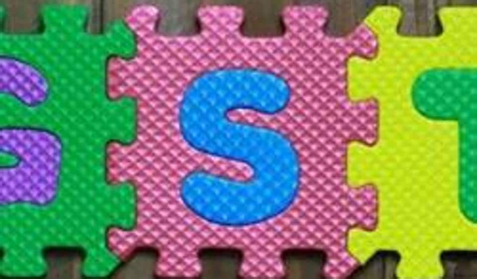 Colourful puzzle block letter with word GST on wood background