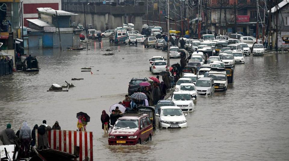 Vehicles make way through a waterlogged street following heavy rains in Srinagar on Thursday.