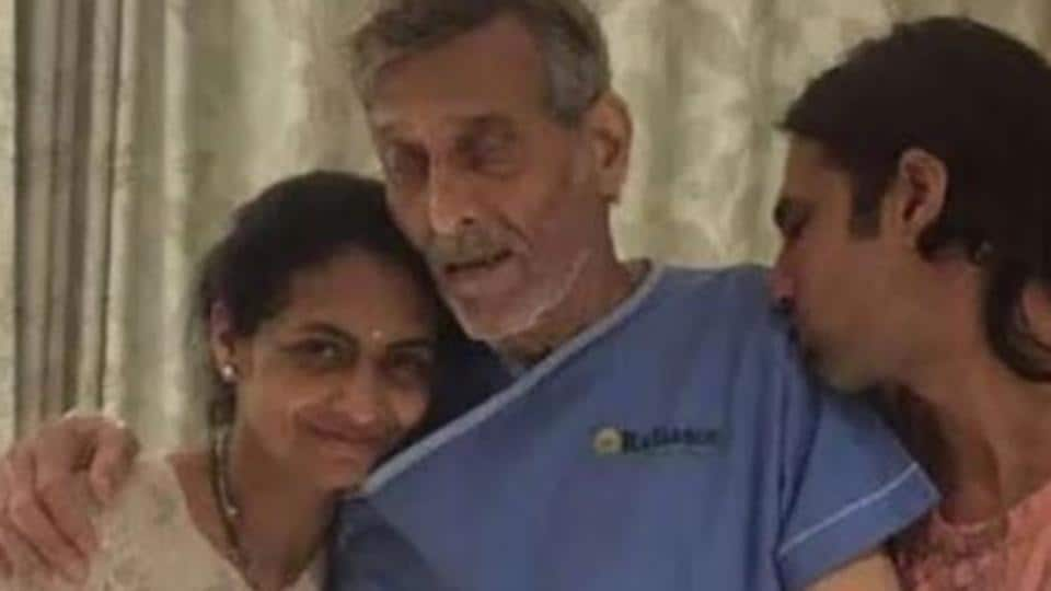 Vinod Khanna is seen standing with the help of family members in a hospital gown.