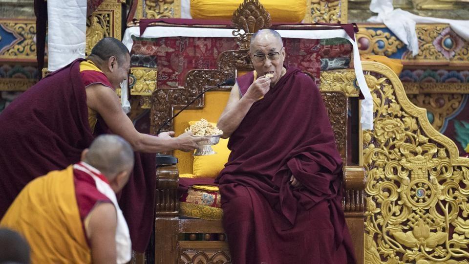 Tibetan spiritual leader the Dalai Lama eats traditional Tibetan cookies upon arrival at the monastery in Tawang on April 7.