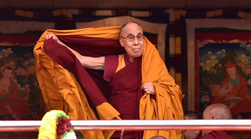 Exiled Tibetan spiritual leader the Dalai Lama adjusts his shawl as he arrives to deliver teachings to Buddhist followers at the Yiga Choezin ground in Tawang District near the India-China border.