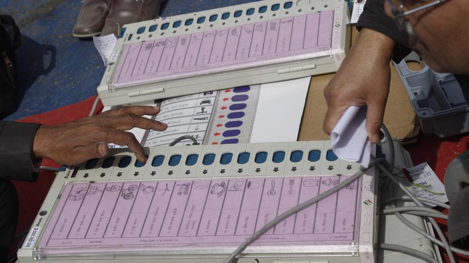 Polling officers check electronic voting machines.
