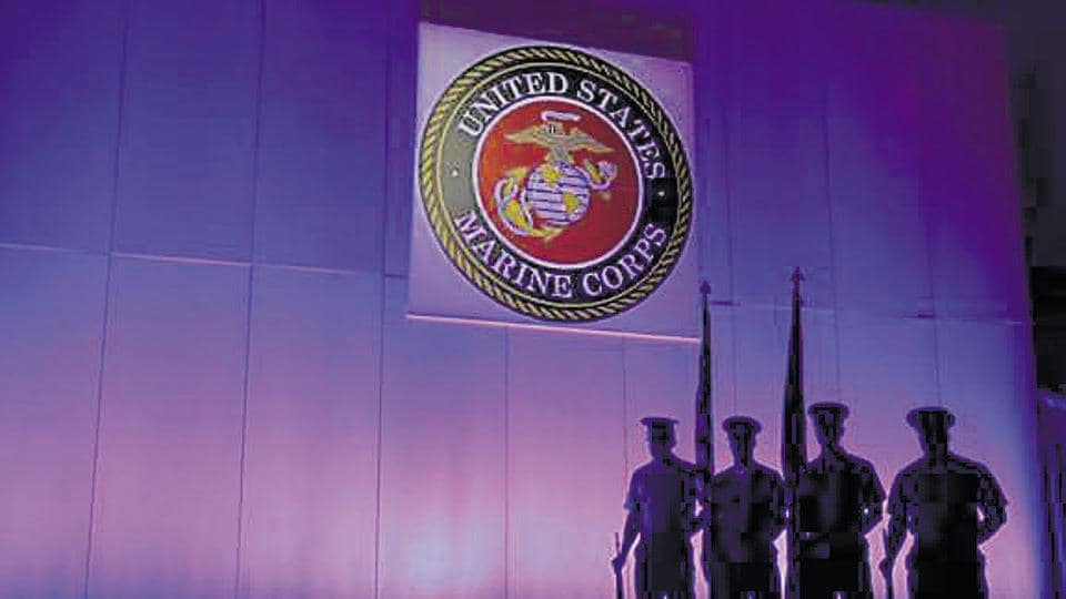 In this May 5, 2014, file photo, a US Marine Corps Color Guard sands under a Marine Corps emblem in Jupiter, Fla.  Two male Marines have been demoted and about two dozen other military members are being investigated in connection with nude photographs that were shared online.