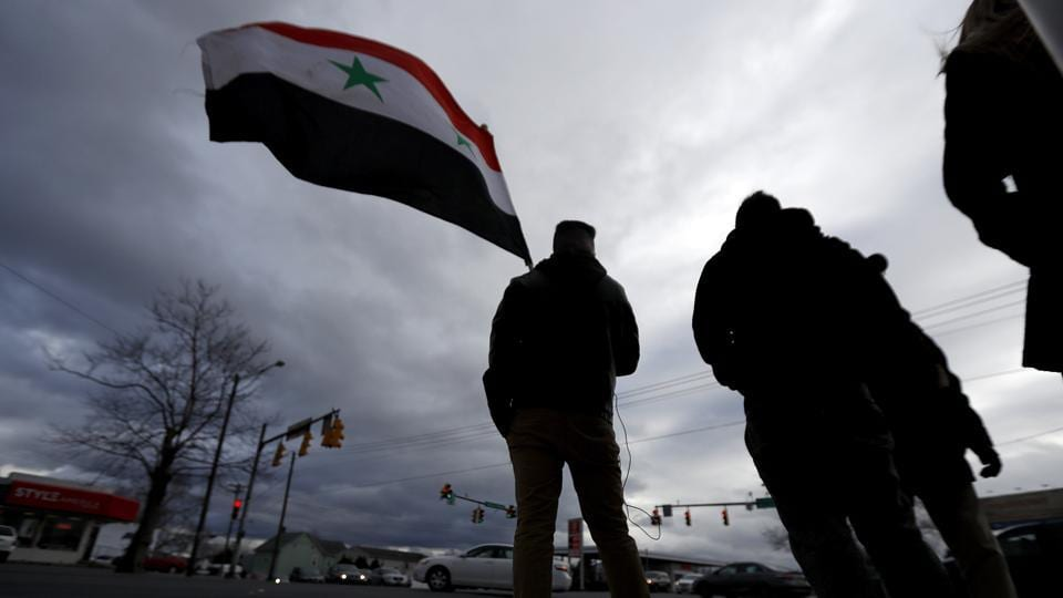 A man holds a Syrian flag during a rally in opposition to the US airstrikes in Syria, in Allentown, Pennsylvania.