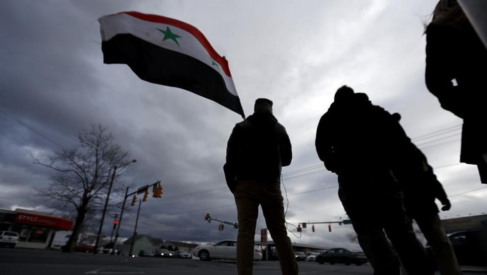 A man holds a Syrian flag during a rally on Friday in Pennsylvania to protest against US airstrikes in Syria.