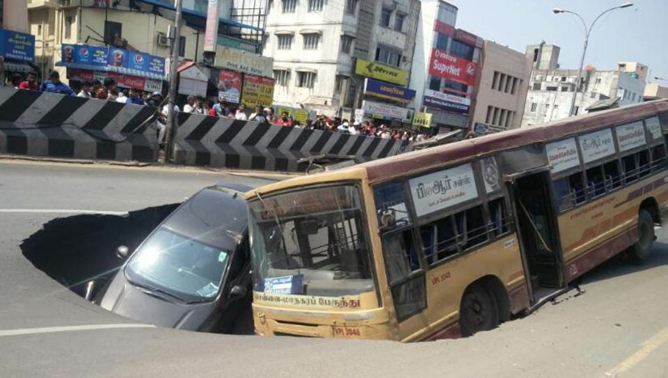 A state bus and a Honda City car trapped in a crater after the Anna Salai road caved in near Church Park street on Sunday afternoon.