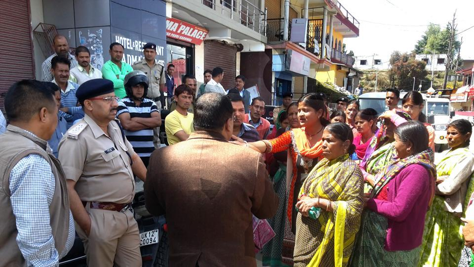 Local administration and excise department officials speak to protesters at Pauri on Sunday.