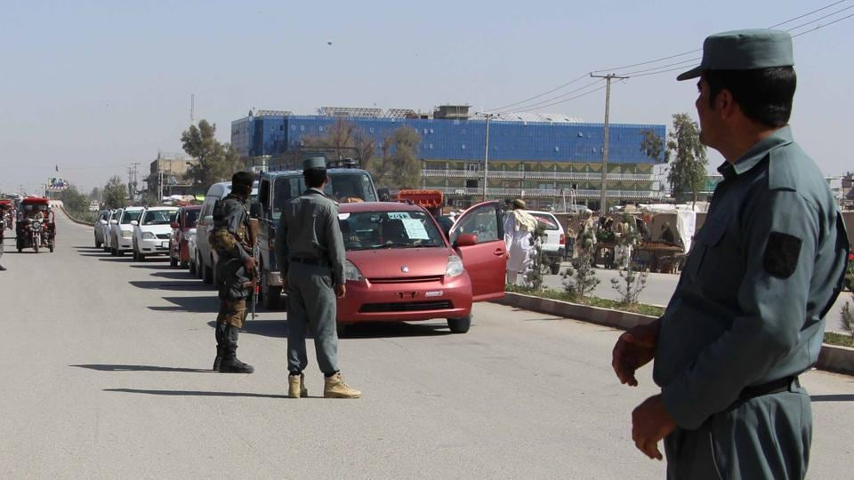 Afghan policemen inspect vehicles at a checkpoint in Helmand province.