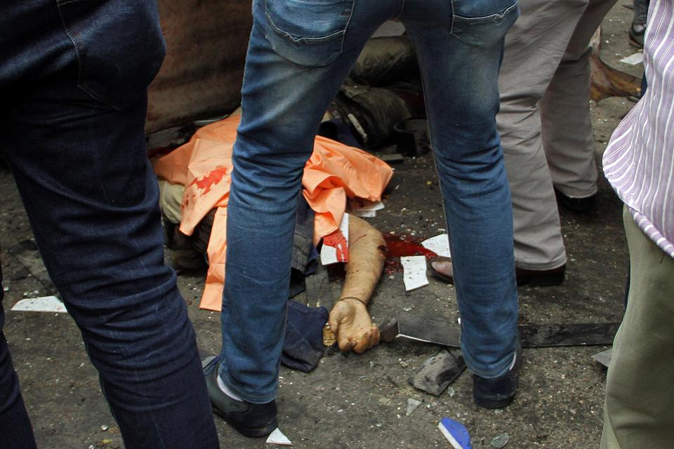Egyptians gather around a body in a street near a church in Alexandria after a bomb blast struck worshippers gathering to celebrate Palm Sunday on April 9, 2017. (AFP)